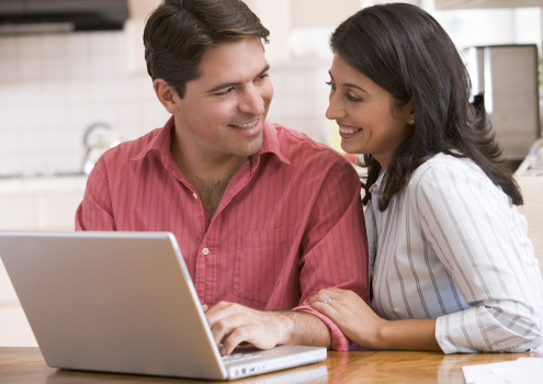 Couples sat with a laptop holding some papers looking worried