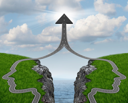 Bridge the gap and bridging the differences between two business partners over a financial cliff to merge together for team success as a strong partnership with two head shaped roads merging as an upward arrow.
