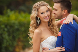 groom - a young dark-haired man in a blue suit and pink wedding tie - butterfly kisses on the cheek bride, blue-eyed - curly blond with long hair in white wedding dress in summer park.