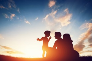 Happy family together, parents with their little child sitting on grass at sunset